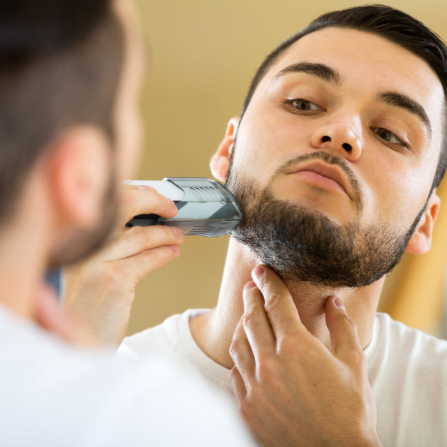 """guy shaving by electric shaver"" stock image"