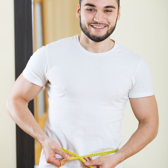 """man measuring his bicep and body"" stock image"