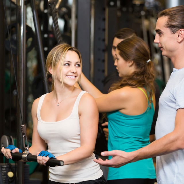 """Adults having strength training under coach control in gym"" stock image"
