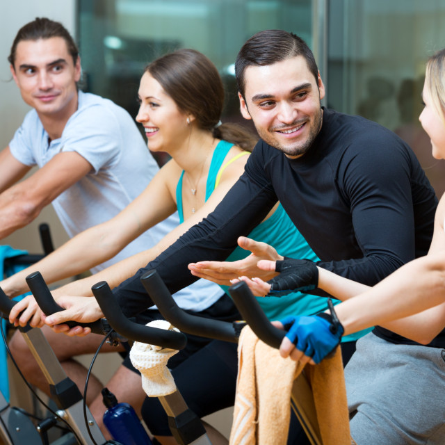 """Active adults riding stationary bicycles"" stock image"