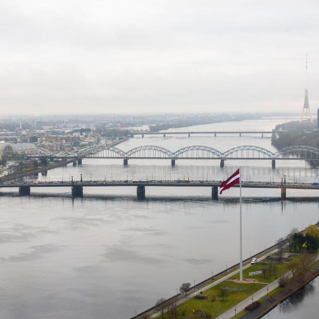 """""""15.11.2018. RIGA, LATVIA. Huge flag of Latvia near river Daugava and Iron bridge."""" stock image"""