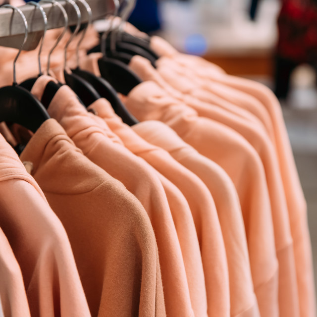 """""""Many One-colour Hooded Sweatshirt On Hanger In Store Of Shopping Center"""" stock image"""