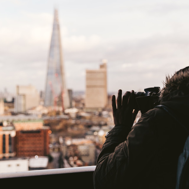 """Man taking photo with camera of modern London winter skyline"" stock image"