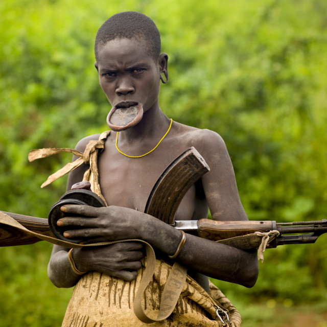 """""""Mursi Tribe Woman With A Lip Plate, A Kalashnikov Rifle And Two Clay Plates..."""" stock image"""