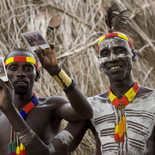 """""""Karo Tribe Men With Body Paintings Showing Polaroids Of The Tribe, Korcho,..."""" stock image"""