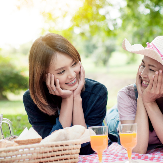 """two asian girlfriends lying on the lawn, Women in park during th"" stock image"