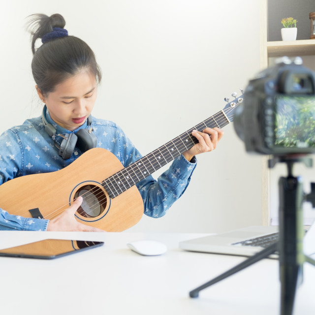 """women sing a song with guitar in hands use camera to broadcast l"" stock image"
