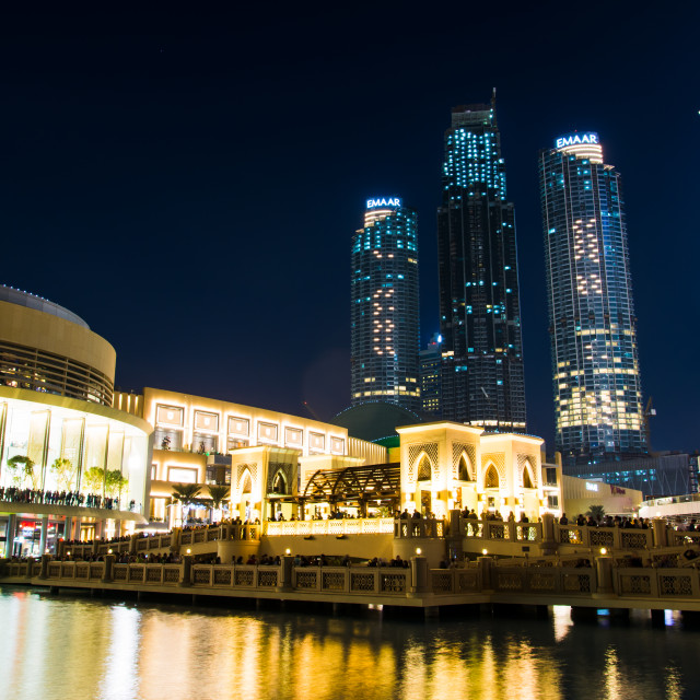 """""""Dubai mall building and neighboring skyscrapers reflected in the fountain at night"""" stock image"""