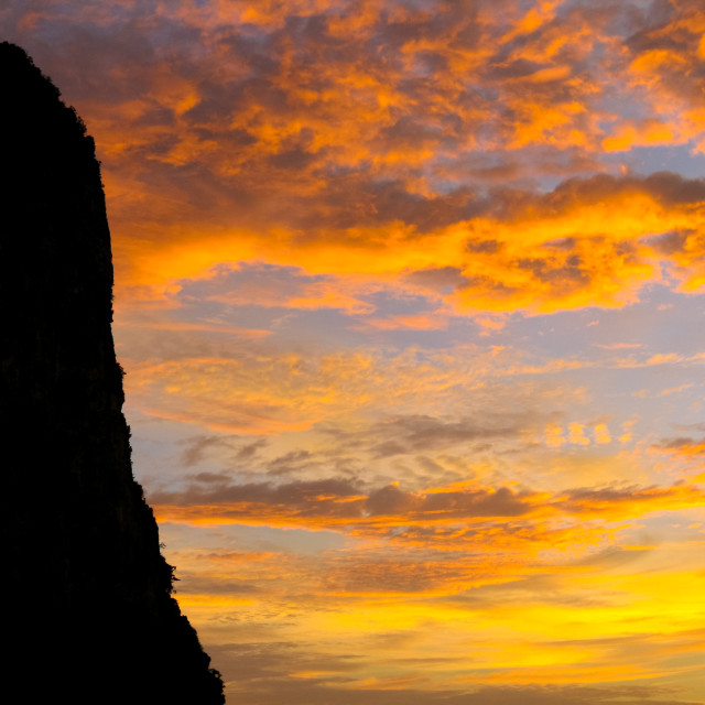 """""""Silhouette of cliff against a sunsetting sky"""" stock image"""
