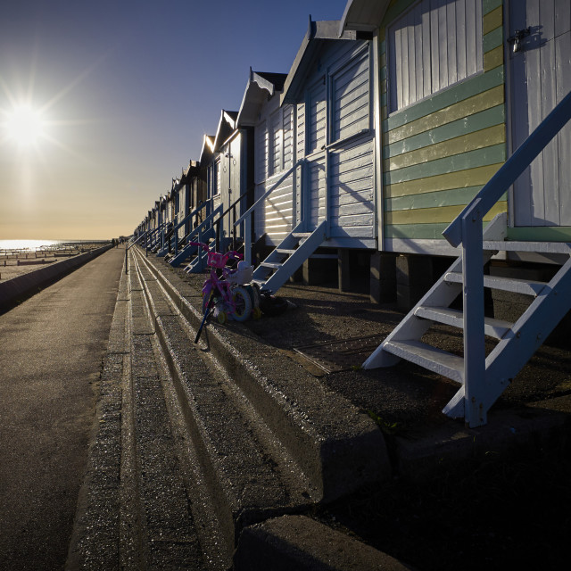 """Frinton beach huts into the sun"" stock image"