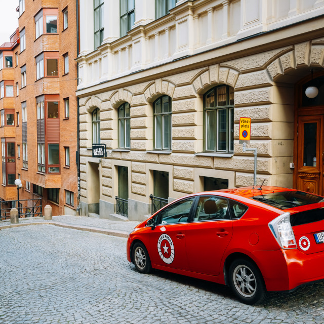 """""""Red color Toyota Prius car parked at sidewalk on the David Bagares street..."""" stock image"""