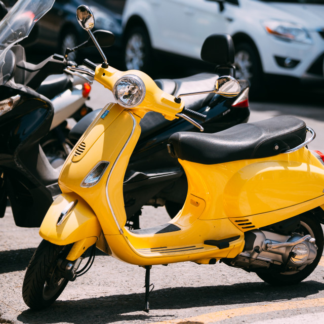 """Yellow Piaggio sprint motor scooter motorbike motorcycle parked in city"" stock image"