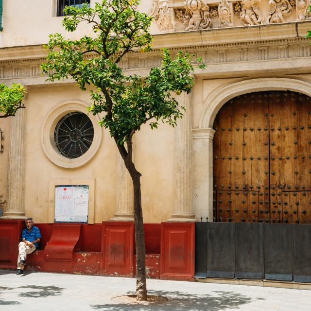 """Man sitting near entrance to church at hospital San Juan de Dios on plaza del..."" stock image"