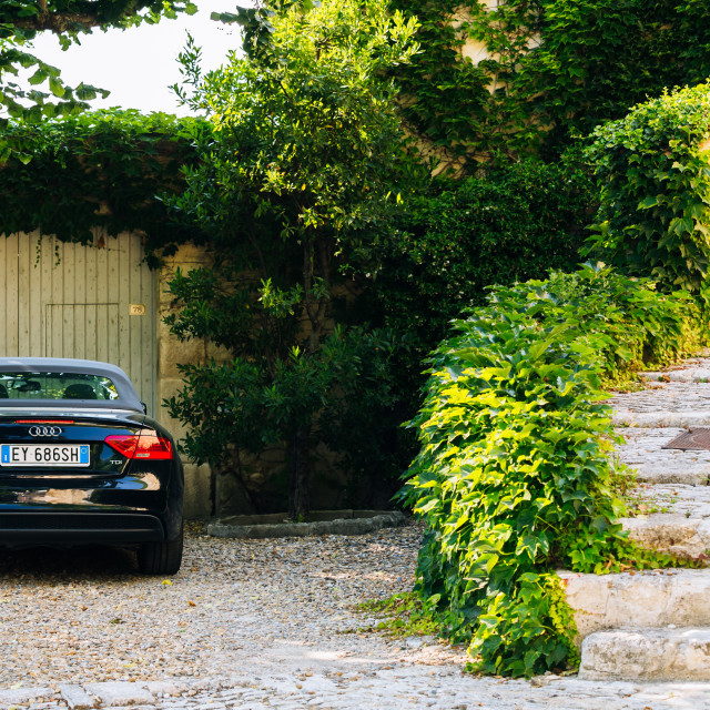 """Black convertible car audi a5 parked at beautiful house in French village..."" stock image"