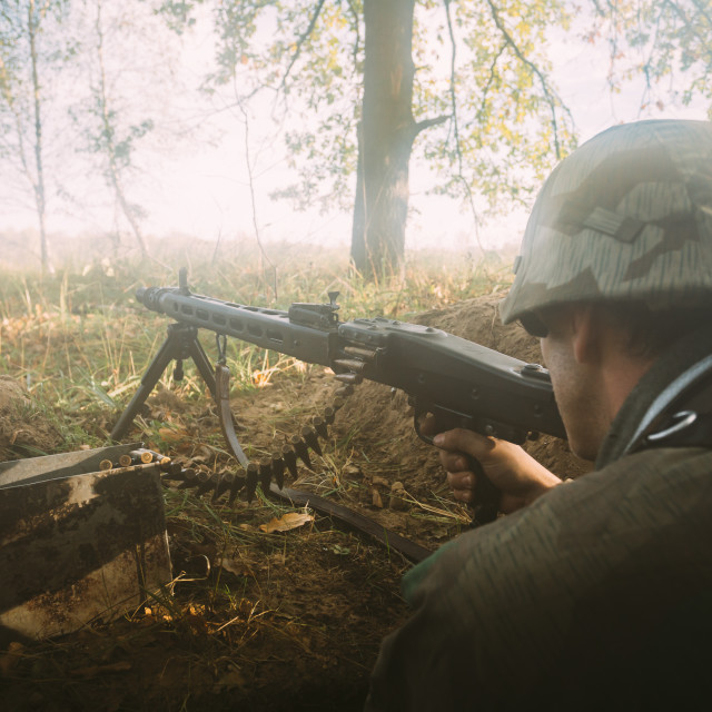 """""""Re-enactor dressed as german wehrmacht soldier aiming a machine gun at enemy..."""" stock image"""