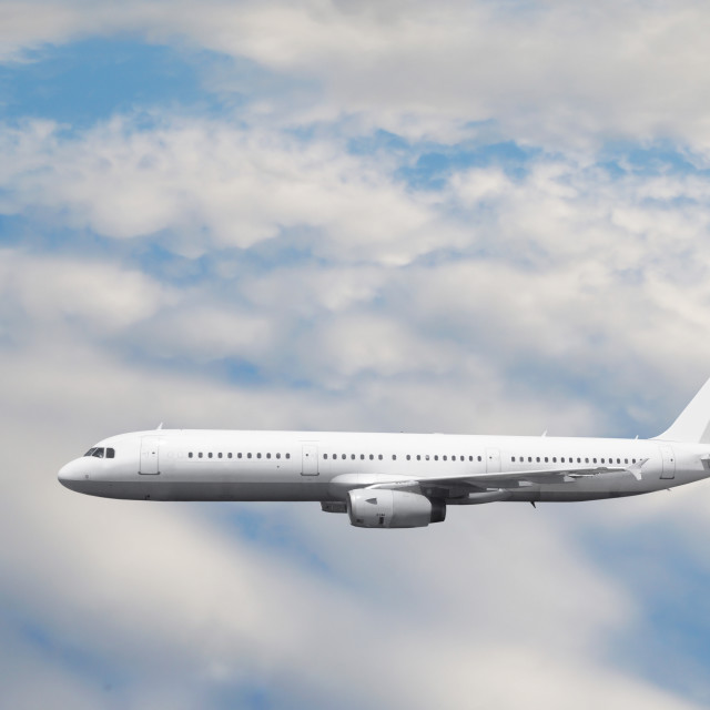 """The white passenger plane flies against a slightly cloudy sky"" stock image"