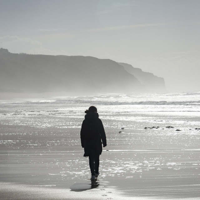 """person walking along an empty beach with footsteps in the sand, silver coast, Portugal,."" stock image"