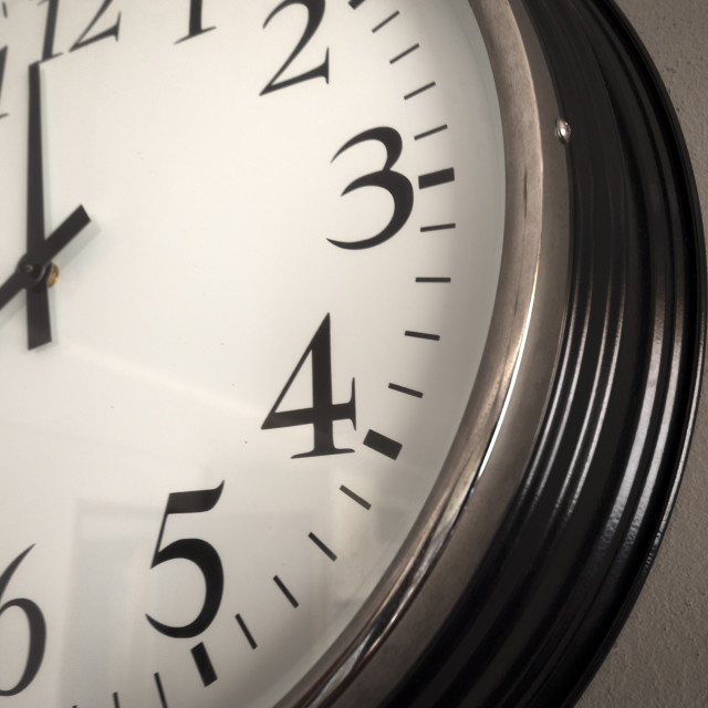 """classic wall clock on a grey wall, close up."" stock image"