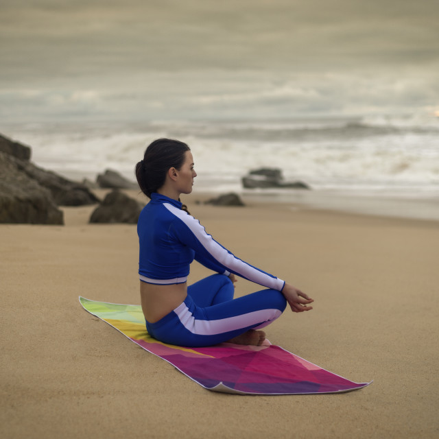 """woman practicing yoga on the beach on a colourful mat, lotus position."" stock image"