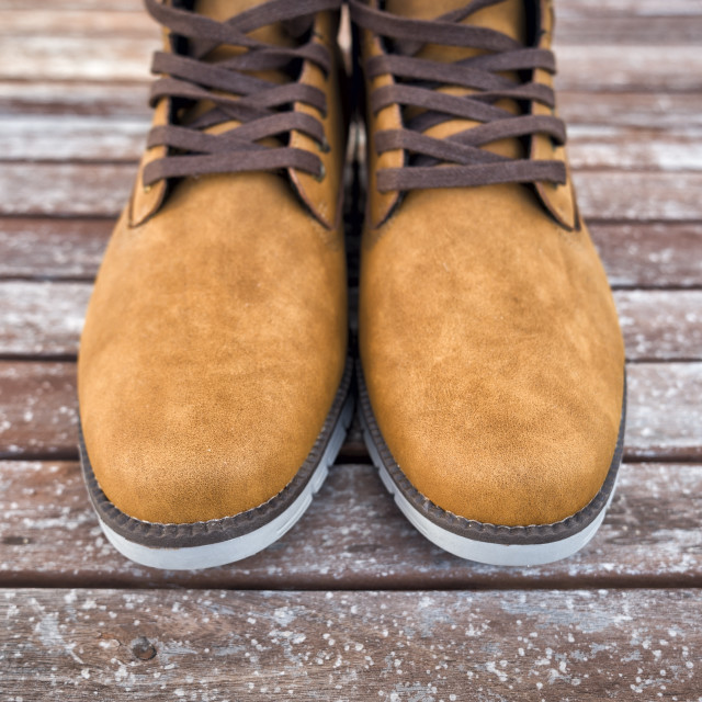 """pair of mens tan suede boots on a wooden floor."" stock image"
