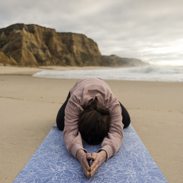 """woman practicing yoga on a mat on a sandy beach."" stock image"