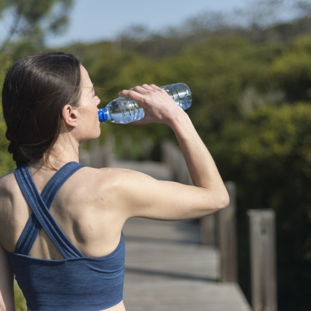 """woman drinking water from a bottle after running. Outside."" stock image"