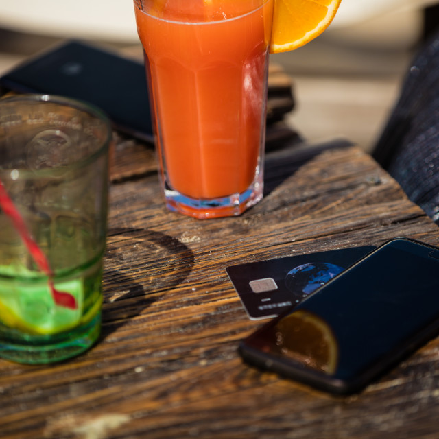 """Orange cocktail and credit card on beach bar"" stock image"