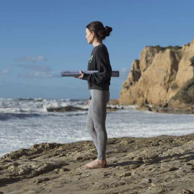 """sporty woman standing on rocks looking out to sea holding a rolled up yoga mat."" stock image"