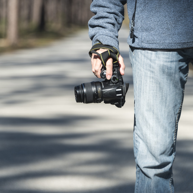 """close up of a man holding a DSLR in his hand by his side. Outside."" stock image"