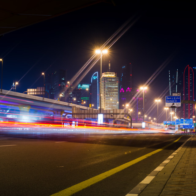 """Dubai street scene with traffic light trails and new city view at night"" stock image"