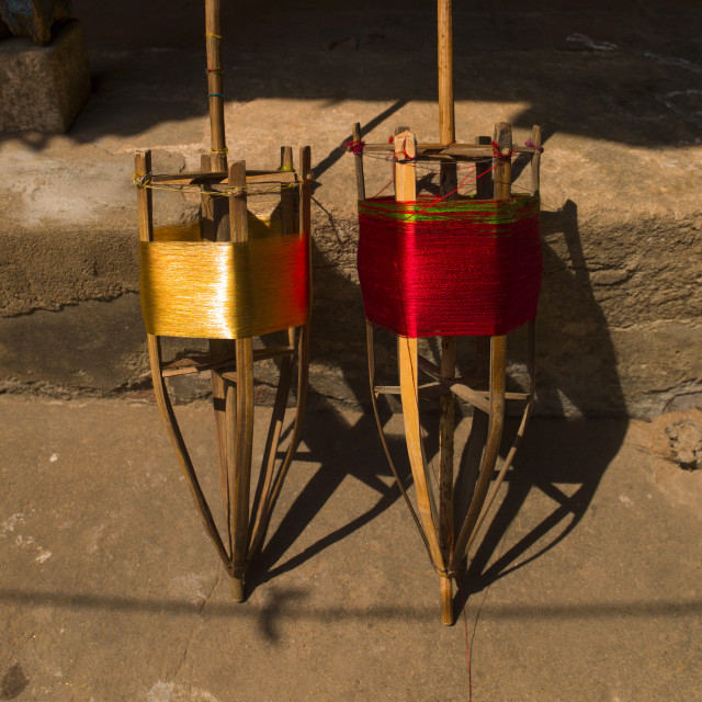 """Traditional Wooden Spools Of Red And Golden Yarn, Kumbakonam, India"" stock image"