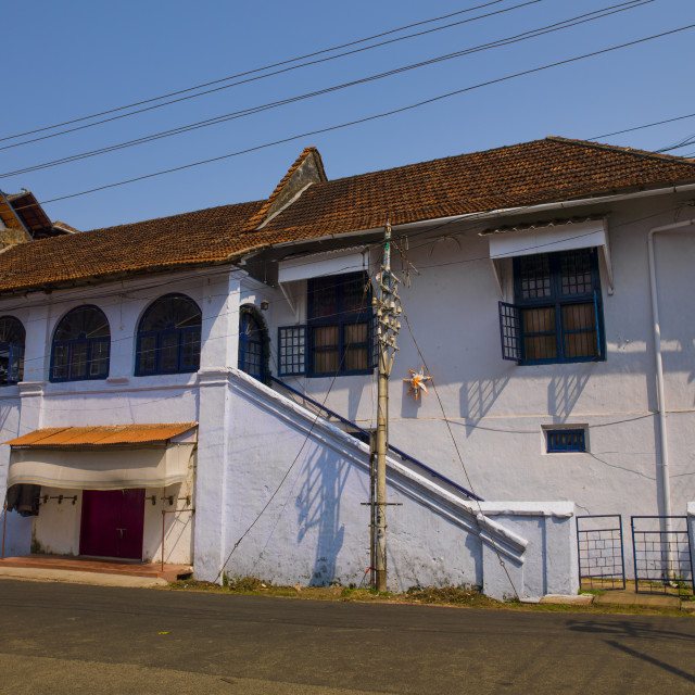 """Front Of A Old White House With Blue Windows, Kochi, India"" stock image"