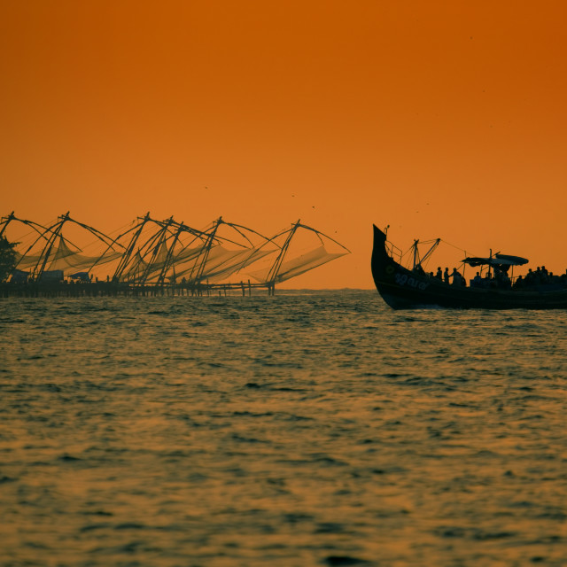 """Boat Sailing Close To Chinese Fishing Nets In Silhouette At Sunset, Kochi, India"" stock image"