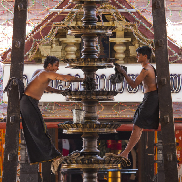 """Two Men Cleaning A Lamp At The Entrance Of A Temple, Kochi, India"" stock image"