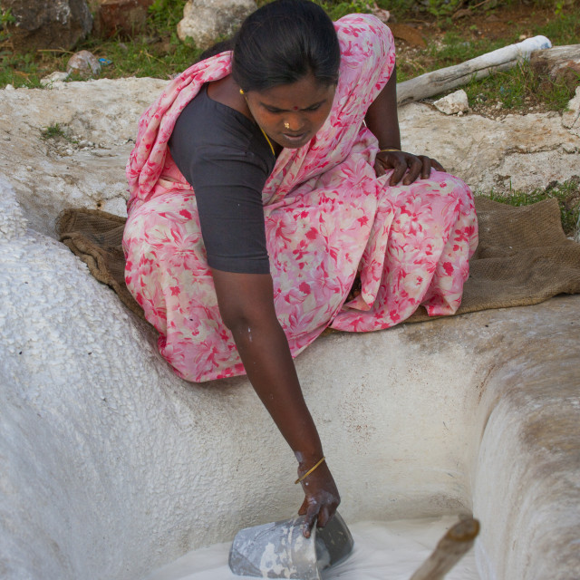 """Squatting Woman Drawing Lime With A Bucket, Madurai, India"" stock image"