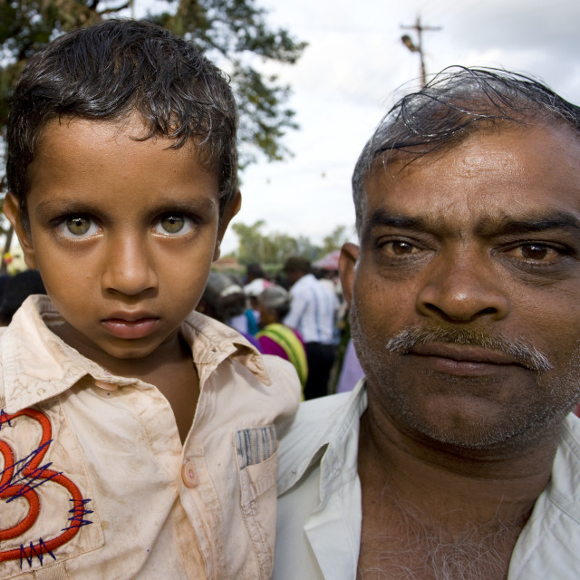 """""""Man Carrying A Boy With Clear Eyes On His Arms Attending Fire Walking Ritual,..."""" stock image"""