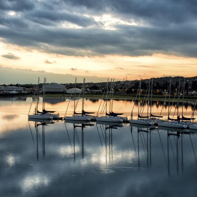 """Yachts moored on a pontoon in Portsmouth Harbour at dusk with a moody sky"" stock image"