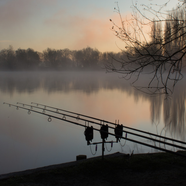 """Sunrise over a lake with fishing rods"" stock image"