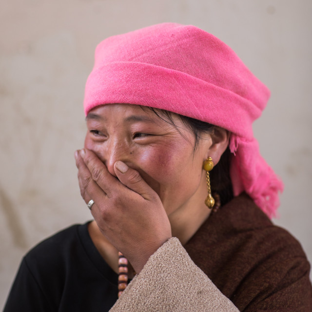 """""""Portrait of a tibetan nomad woman with a pink headwear laughing, Qinghai..."""" stock image"""