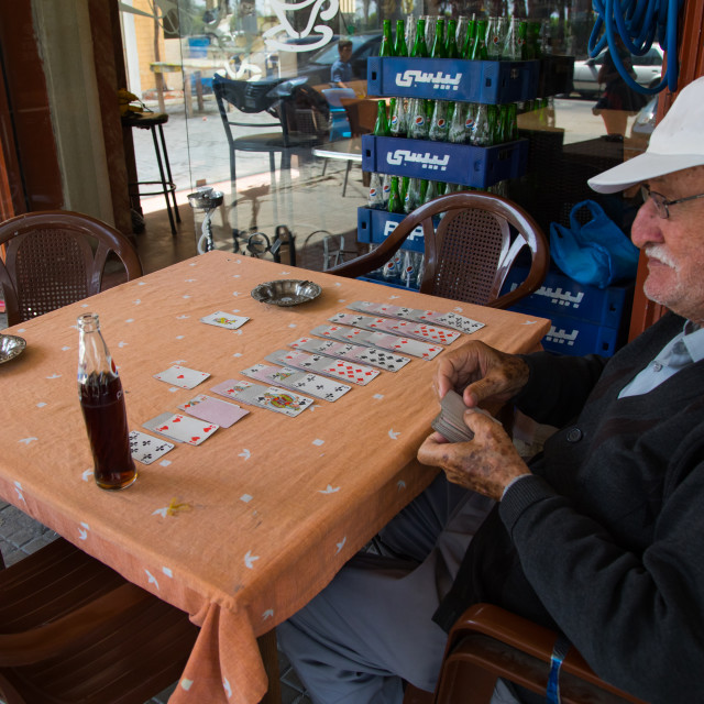 """Old man playing cards alone at cafe table, North Governorate, Tripoli, Lebanon"" stock image"