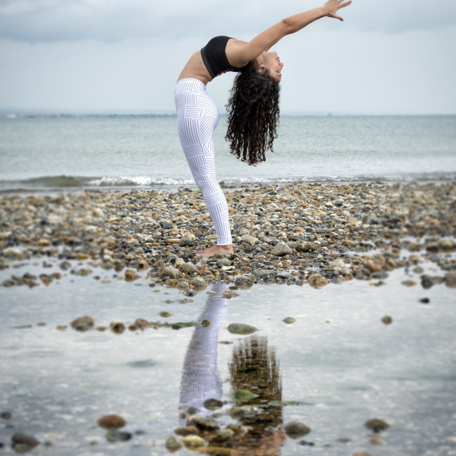 """woman practicing yoga by the sea"" stock image"