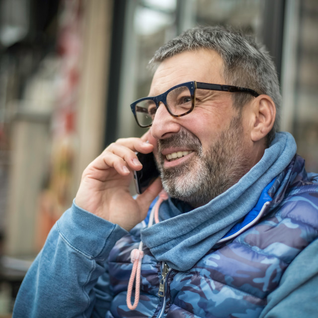 """""""Middle-aged man with a gray beard and glasses talking on a mobil"""" stock image"""