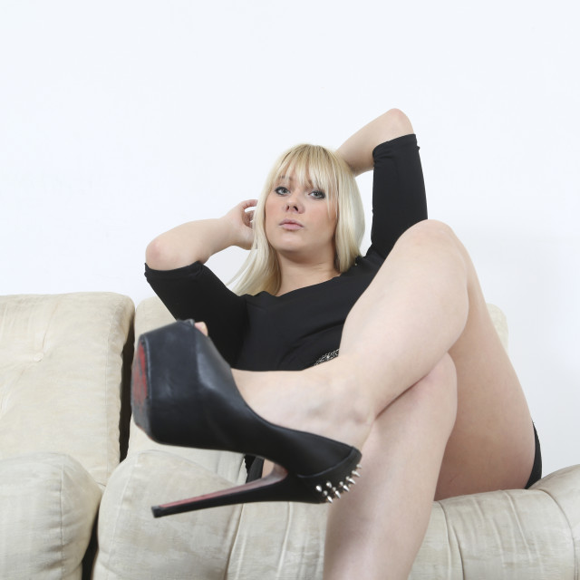 """""""Blonde getting dressed on sofa"""" stock image"""