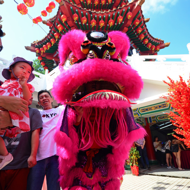 """""""Kuala Lumpur, Malaysia - February 16, 2018: Man and child at lion dance during Chinese New Year celebration in Thean Hou Temple."""" stock image"""