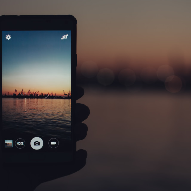 """""""Tourist taking photo of sea harbor with mobile device at sunset"""" stock image"""