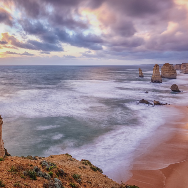 """Twelve Apostles rock formation with a pink, blue and yellow sunset sky, Australia"" stock image"
