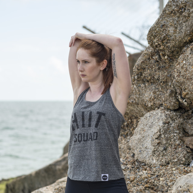 """woman wearing sportswear stretching by the sea"" stock image"