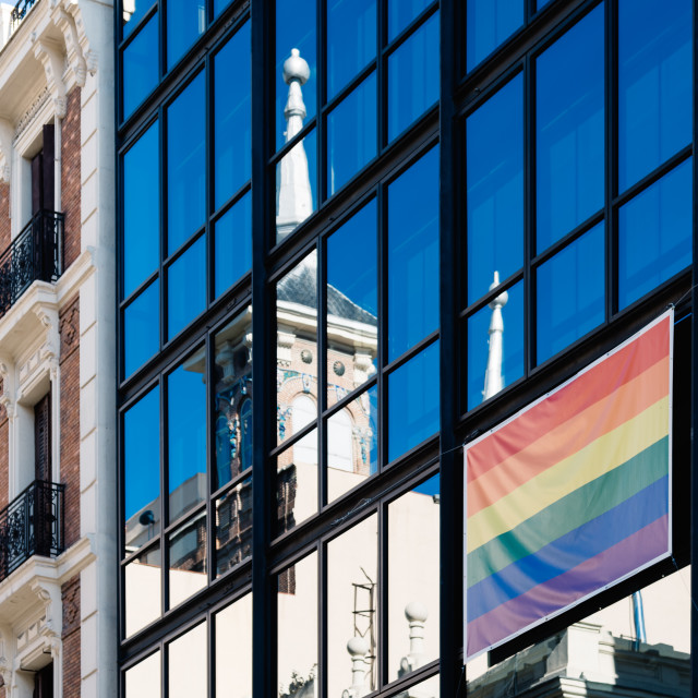 """""""Rainbow gay flag in glass facade of building"""" stock image"""