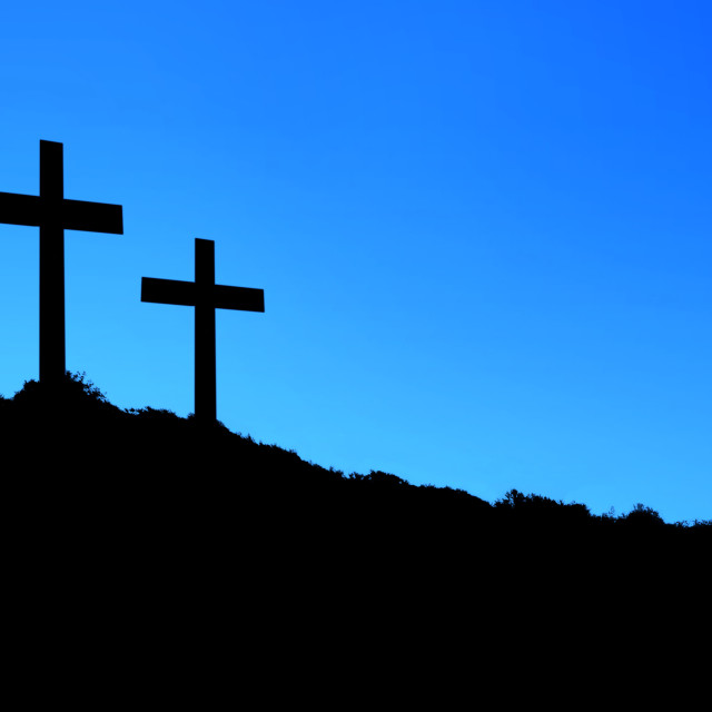 """Religious illustration with three crosses on hill and blue sky"" stock image"