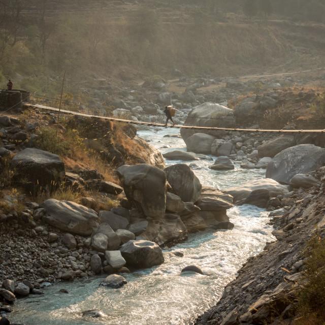 """Person Crossing a Swinging Bridge"" stock image"